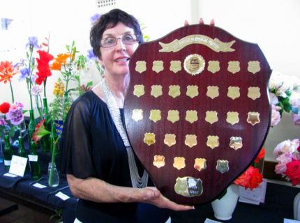 Past president Lyn Dahl holding the Joy Bowley Perpetual Trophy for Supreme Champion Dairy Goat